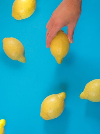 Hand holding a lemon on blue background