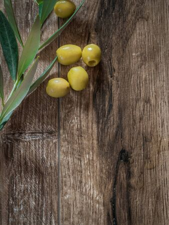 Pitted olives with leaves on wood background with copy space Фото со стока