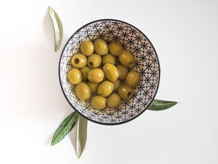 Pitted olives in a bowl on white background