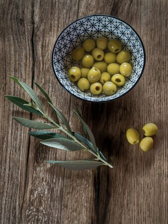 Pitted olives in a bowl with leaves on wood background