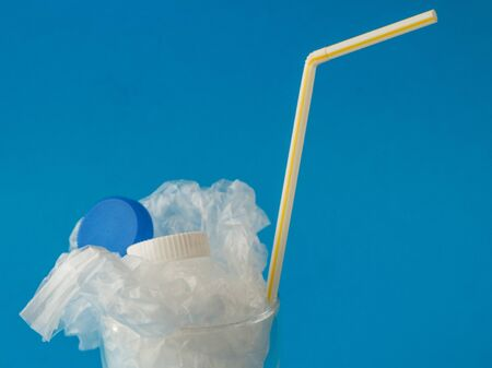 Glass with plastic inside on blue background with copy space - drinking plastic environmental concept