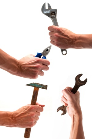 four hands with various equipment (wrench, hammer, pliers) isolated white