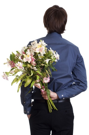 Man hold bouquet of flowers behind his back   isolated on white Stock Photo