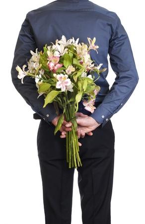 Man przytrzymaj bukiet bukiet kwiatów za plecami samodzielnie o. Zdjęcie Seryjne