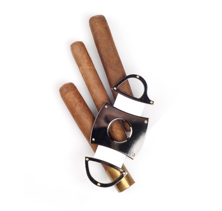 Cigars and a cutter that lay on it isolated on white background