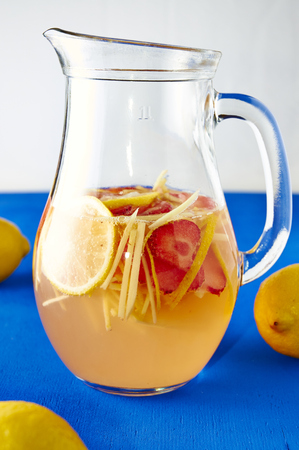 Fresh ginger lemonade with strawberry in pithcer photo