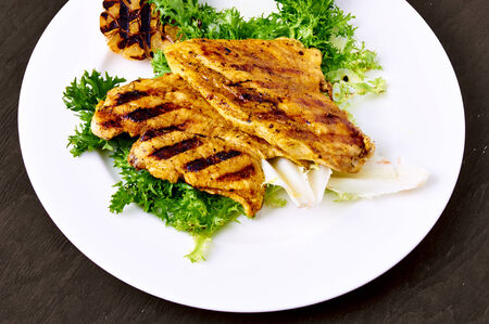 Grilled chicken breast, on a bed of lettuce