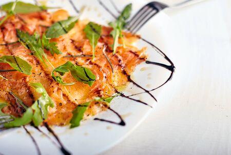 balsamic: Salmon carpaccio on white plate with balsamic vinegar
