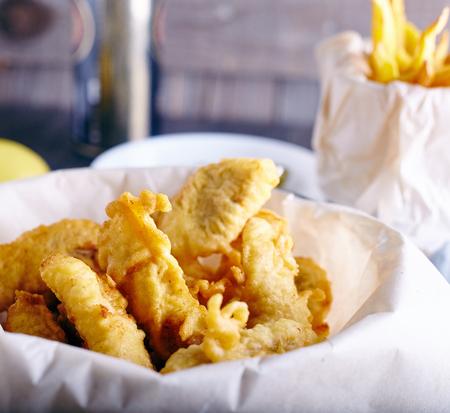 fish and chips: Pescado y patatas fritas de pescado blanco en el papel sobre fondo de madera