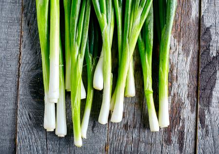 cebolla: Manojo de cebollas verdes frescas en el fondo de madera oscura o neutral