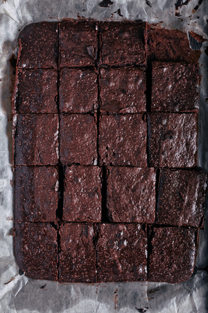 Homemade cut in squares chocolate brownie in backing pan just from oven on dark wooden background. Top view on baking sheet with dessert