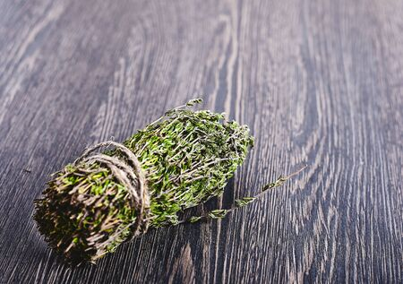 Bunch of thyme tied by a rope on a dark wood background