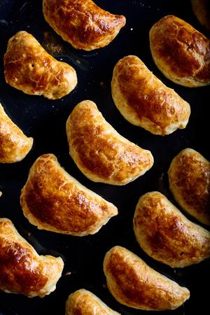 Homemade empanadas - argentine roasted meat pies on wood background Stock Photo