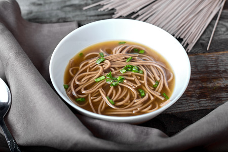 soba noodles: Spicy asian soup with soba noodles, ginger, chili, green onion on wood background