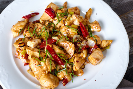 Kung Pao Chicken with Peppers, peanuts and Veggies and sticky glance sauce on wood background Stock Photo