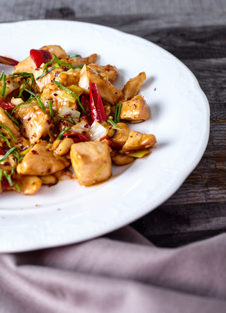 Kung Pao Chicken in white plate on Wood Background with napkin near it