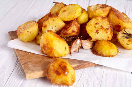 Roast potatoes seasoned with salt, garlic and provance herbs on wood background