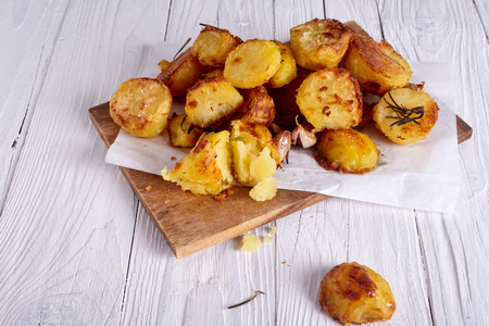 uk cuisine: Perfect roasted potatoes with spices and herbs on wood board