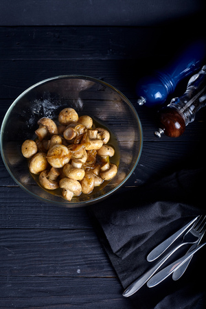 Roasted marinade mushrooms in bowl on dark background with salt and paper near it. Stock Photo