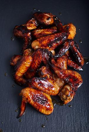 Alas fritos o asados ??de pollo con salsa de miel en el fondo de piedra oscura