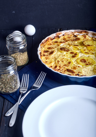 Potato gratin with cream, eggs and cheese on dark wood background.