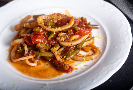 Stewed squid rings with tomato sauce and chilli in white plate. Stock Photo
