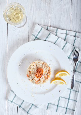 Plate of Risotto with shrimp and glass of white wine on white wood background