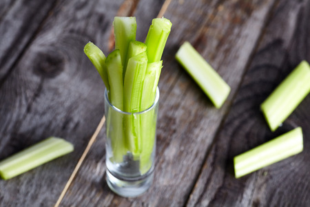 Cutted celery sticks in small glass on wood background. Snack for buffalo wings