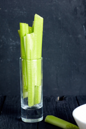 Cutted celery sticks in small glass on black background. Snack for buffalo wings Stock Photo