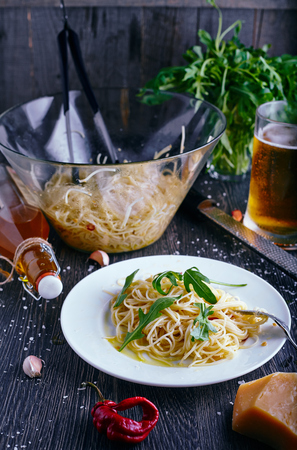 near beer: Pasta with garlic, oil, chilli and parmesan on wood background. Beer glass on back and olive oil bottle near it.