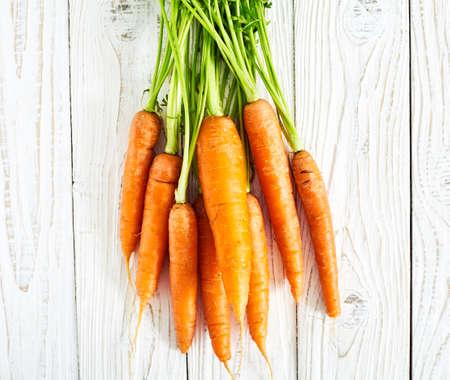 haulm: Fresh carrots with green leaves stalks or haulm on white  wood background