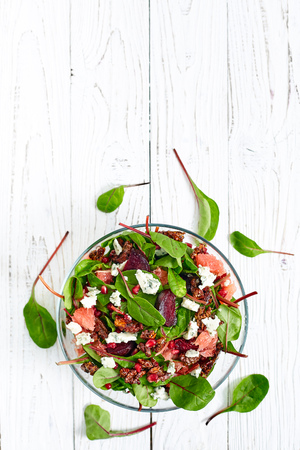 baby spinach: Top view of healthy beet and baby spinach salad with pomergranate, blue cheese Roquefort, gorgonzola grapefruit, caramelized nuts and citrus vinaigrette dressing. White wood background, text place Stock Photo