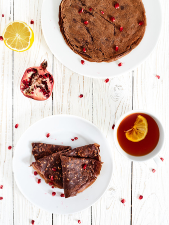 maslenitsa: Chocolate crepes or pancakes with oatmeal and pomergranate. White wood table with healthy homemade sugar and eegs free breakfest dish on white plate, with a cup of tea with lemon and pomegranate near Stock Photo