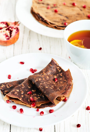 free dish: Chocolate crepes or pancakes with oatmeal and pomergranate. Healthy homemade sugar and eegs free breakfest dish. White wood background, white plate, a cup of tea with lemon and pomegranate on back. Stock Photo