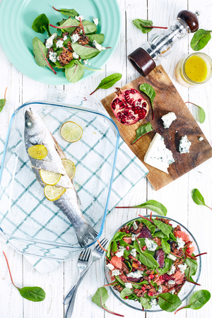 baby spinach: Top view of healthy dinner with beet and baby spinach salad , roasted seabass fish, feta cheese, pomergrat and citrus vinaigrette dressing. White wood background Stock Photo