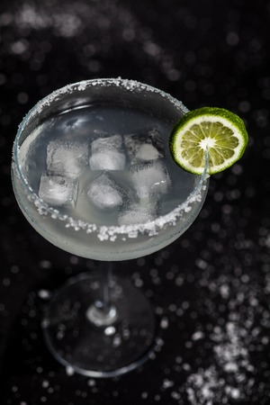 margarita glass: Classic mexican margarita cocktail on black background. Margarita glass full of ice, salt and lime on side. Black background with whites sea salt spots. Stock Photo