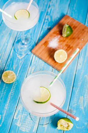 margarita glass: Classic Margarita Cocktail in margarita glass served with lime on aqua wood table. Cocktail ingredients: tequila, lime juice, orange liquor, ice and sea salt