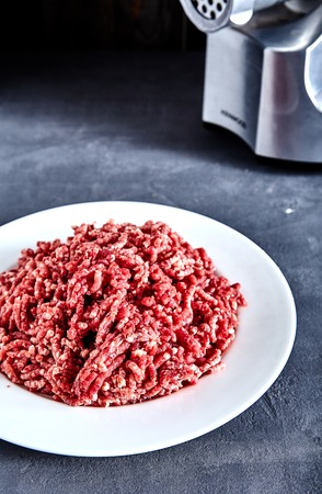 Pinky raw ground beef on a white plate with meat grinder near it. Ground beef can be used to cook hamburgers, chili con carne or other dishes. Textured stone background.