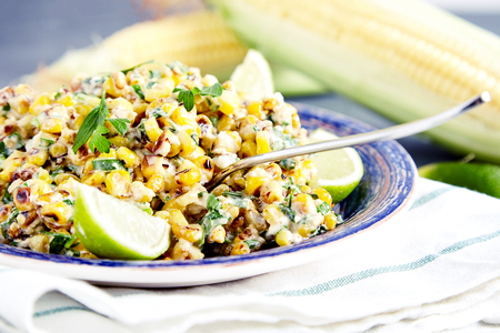 corn salad: Close up of homemade vegetarian mexican street food corn salad with cilantro, lime, mayonnaise, garlic, chili and cheese on blue plate on stone background. Two corn heads on blured background Stock Photo