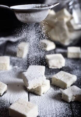 sugar powder: Marshmallows sprinkled with sugar powder from sieve that looks like falling snow on black wooden background Stock Photo