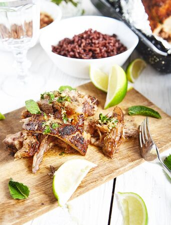 mojo: Sliced cuban style slow roasted pork shoulder in mojo marinade and sauce on wood board with limes and mint near it . White wood background with brown rice bowl and big roasted shoulder in pan on back Stock Photo