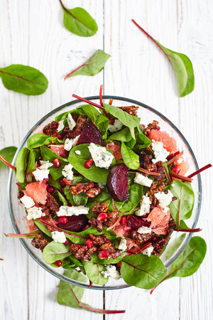pomergranate: Top view of healthy beet and baby spinach salad with pomergranate, blue cheese Roquefort, gorgonzola grapefruit, caramelized nuts and citrus vinaigrette dressing. White wood background Stock Photo