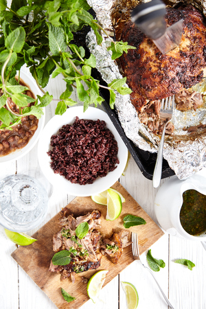 Top view of white wood table with sliced cuban style slow roasted pork shoulder in mojo marinade on wood board, roasted beans, brown rice and pan with pork shoulder with knife in it. Stock Photo