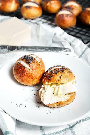 pretzel: Homemade baked sliced pretzel bun with poppy seeds and butter on it on white plate. Group of many pretzel buns on back. This buns is german cuisine dish, ideal for lunch or breakfest with tea. Stock Photo