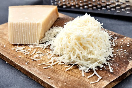 parmezan: Piece and grated parmigiano reggiano or parmesan cheese on wwood board on checkered napkin . Grated parmesan uses in pasta dishes, soups, risottos and grated over salads.