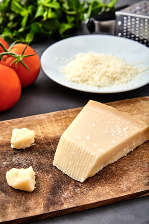 grated parmesan cheese: Piece of parmigiano reggiano cheese and grated parmesan cheese on wood board on stone background. Tomatoes and grater on back. Parmesan uses in pasta dishes, soups, risottos and grated over salads. Stock Photo