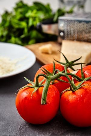 queso rallado: Rama de tomates rojos frescos con gotas de agua sobre y parmesano o queso parmigiano reggiano en la parte posterior con el rallador y el queso rallado en un plato blanco y haz de menta. Concepto de ingredientes de la cocina italiana
