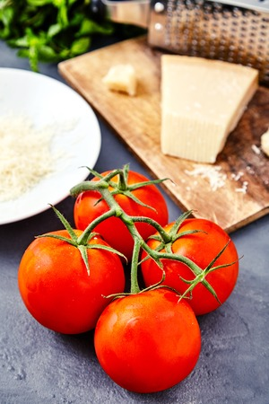 grated cheese: Branch of fresh red tomatoes with water drops on and parmesan or parmigiano reggiano cheese on back with grater and grated cheese on white plate and mint beam. Concept of italian cuisine ingredients