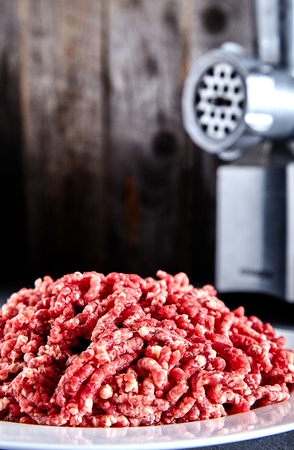 pinky: Pinky raw ground beef on a white plate with meat grinder near it. Ground beef can be used to cook hamburgers, chili con carne or other dishes. Wood background.