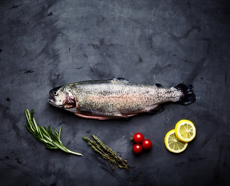 saturated color: Raw fresh gutted rainbow trout with cherry tomatoes, slices of lemon, sprigs of rosemary and thyme. Preparation for cooking delicious fish on dark background. Top view, saturated color, place for text